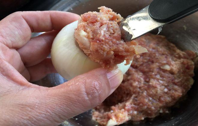 玉ねぎにひき肉を詰める作業